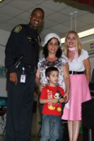 Miami-Dade Schools Police Chief Ian A. Moffett (left) poses with Ismary Rey and her son Robert Docina, they are joined by Yamila Carballo, principal at The English Center where Ismary is a student. Moffett stopped by to deliver Walmart gift cards donated by The Miami Herald readers for Ismary and her family. Ismary was featured in the paper as part of their annual holiday series Wish Book. For more than 30 years, the Miami Herald Wish Book Program has spotlighted the needs of less fortunate individuals in South Florida.